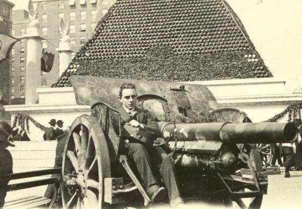 Német 7,7 cm-es Feldkanone 96 mintájú ágyúval pózoló amerikai férfi, háttérben az egyik Pickelhaube-piramis. Forrás: usmilitariaforum.com