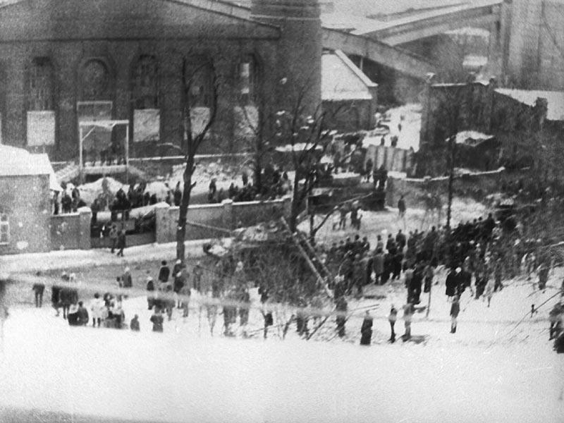 Sztrájkoló tömeg a bánya területén és annak falai előtt. A tömeg sorfala között a katonaság tankja. (Forrás: Archívum IPN)