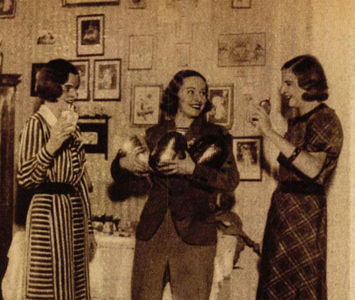 """'33 húsvétján férfi módi locsolkodó körutat tervezve meglátogatta kolleganőit. A képen Radocza Magda és Imrédy Magda """"visszalocsolják"""" a férfiöltözékbe bújt Lilit.(Színházi Élet 1933/18. sz. 65.)"""