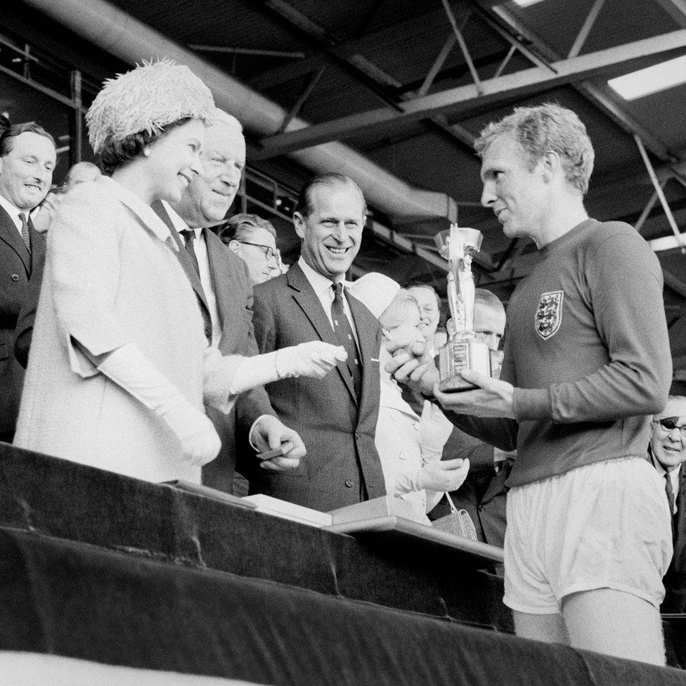 Anglia kapitánya, Bobby Moore tartja a Jules Rimet trófeát, amelyet II. Erzsébet királynőtől vesz át, miután a Wembley-i világbajnoki döntőben 4-2 arányú győzelmet szerzett a Nyugat-Németország ellen.
