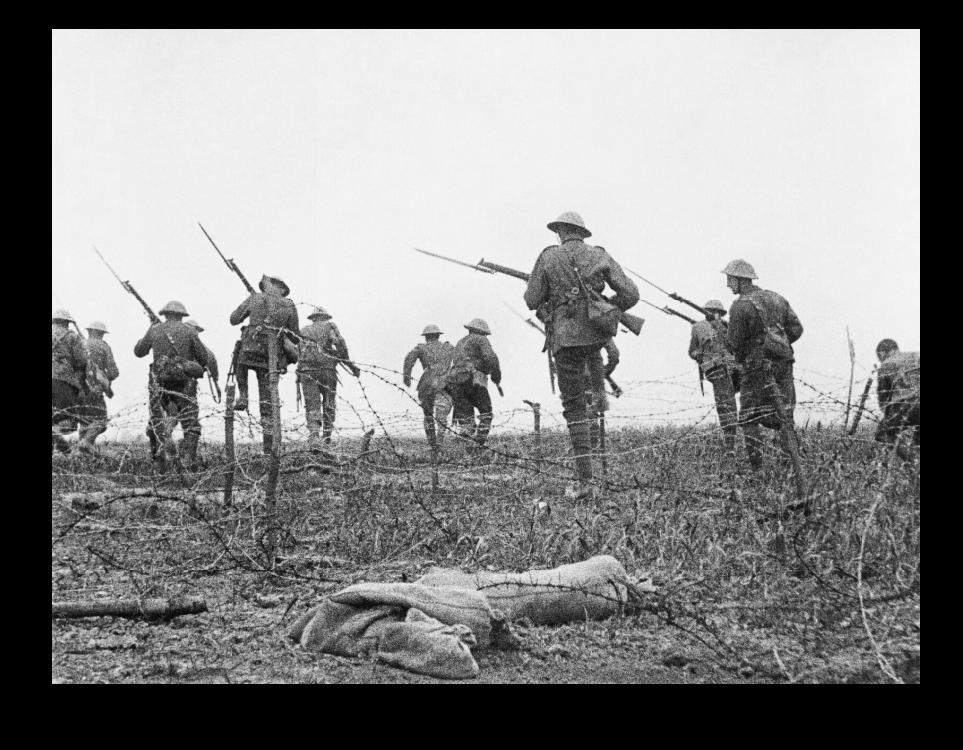 Brit katonák indulnak rohamra saját szögesdrótakadályaik között. (Beállított) kép a somme-i csatából, 1916. Forrás: Imperial War Musem (Q 65408)