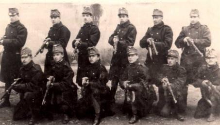 Főiskolás hallgatók önkéntesként a cs. és kir. esztergomi 26. gyalogezrednél. Az álló sorban balról harmadik Király Lajos. A tizenkét fiatal közül hat elesett. Forrás: