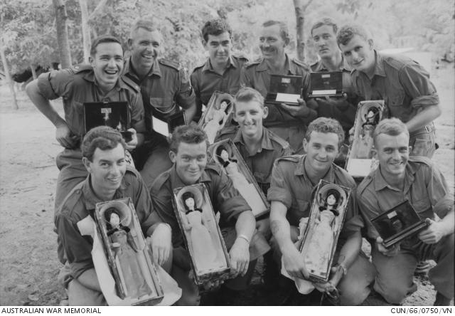 A D század katonái, a dél-vietnami kormánytól hősies helytállásukért kapott babákkal és szivarosdobozokkal 1966. szeptember 2-án. Kitüntetést azért nem kaphattak, mert idegen kitüntetések átvételét tiltották hagyományaik.